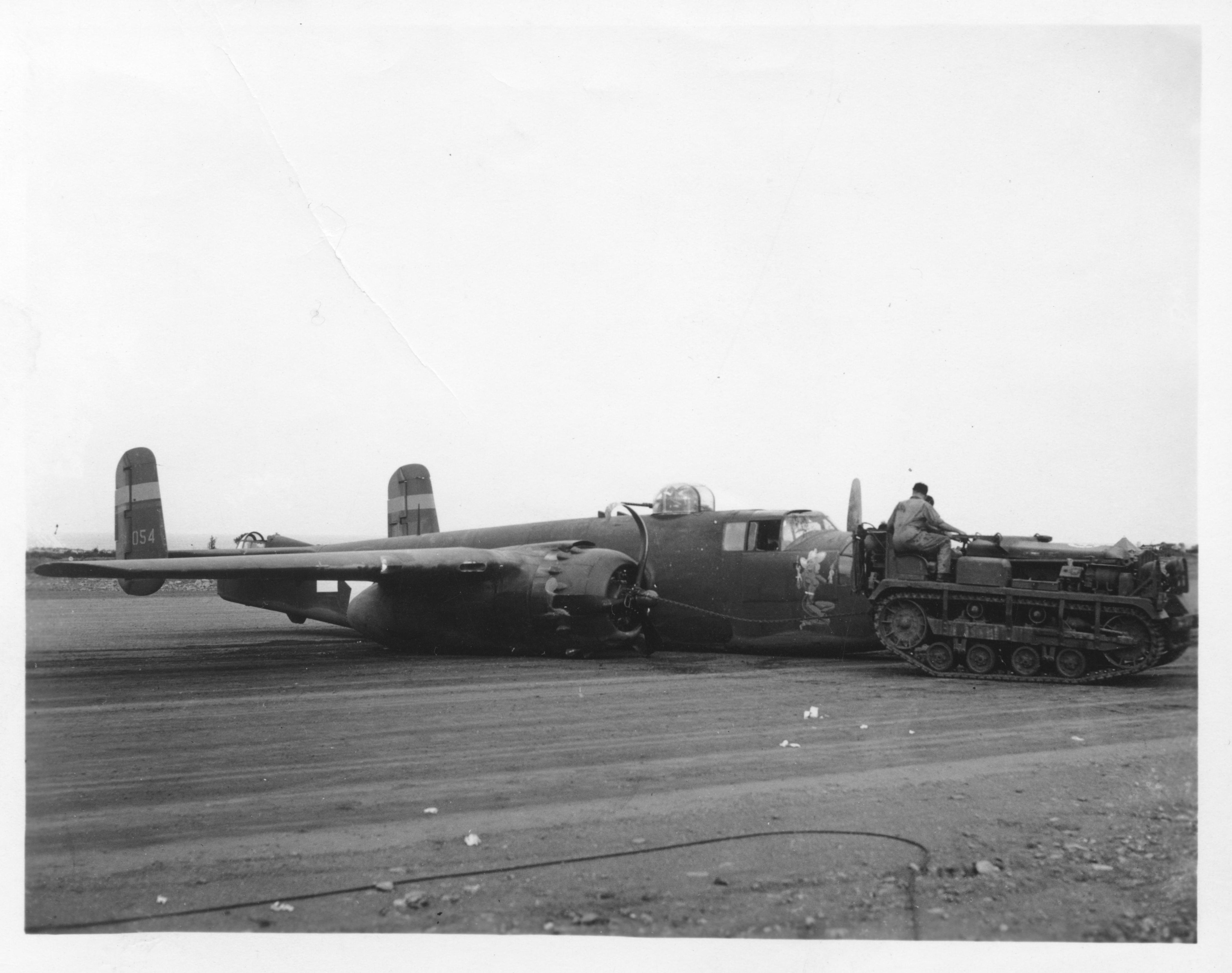 gtb_plane.jpg - Glenn T. Black's B-25J, June 22, 1944, at the end of his 56th mission, being towed off the runway by a cletrac